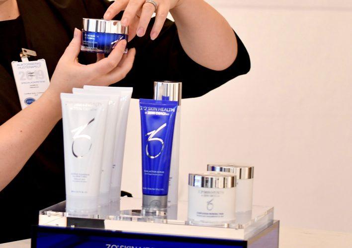 Produktställ med produkter från Zo Skin Health och händer som håller i en burk